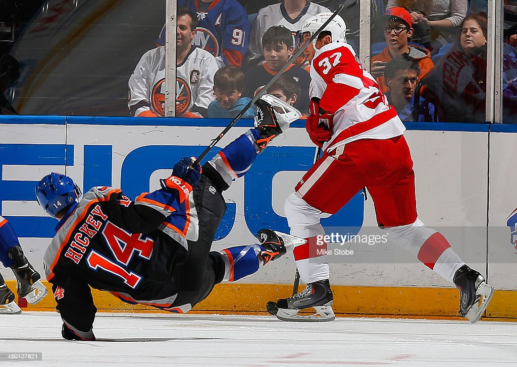 Thomas Hickey #14 of the New York Islanders is sent to the ice by <a gi-track='captionPersonalityLinkClicked' href=/galleries/search?phrase=Mikael+Samuelsson&family=editorial&specificpeople=203085 ng-click='$event.stopPropagation()'>Mikael Samuelsson</a> #37 of the Detroit Red Wings at Nassau Veterans Memorial Coliseum on November 16, 2013 in Uniondale, New York. Islanders defeated the Red Wings 5-4 in a shootout.