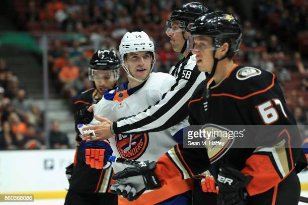 Thomas Hickey of the New York Islanders pushes Rickard Rakell of the Anaheim Ducks during the third period of a game at Honda Center on October 11...