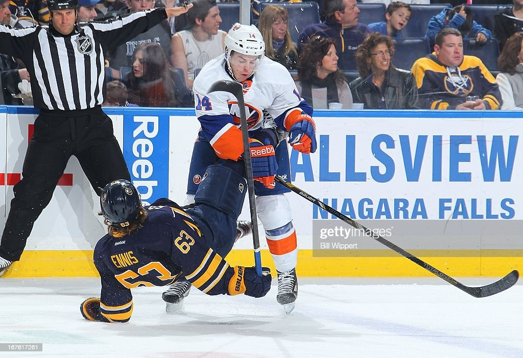 Thomas Hickey #14 of the New York Islanders sends Tyler Ennis #63 of the Buffalo Sabres to the ice with a stiff check on April 26, 2013 at the First Niagara Center in Buffalo, New York.