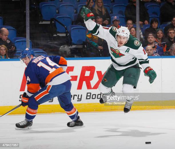 Thomas Hickey of the New York Islanders sends Zach Parise of the Minnesota Wild into the air during the first period in an NHL hockey game at Nassau...