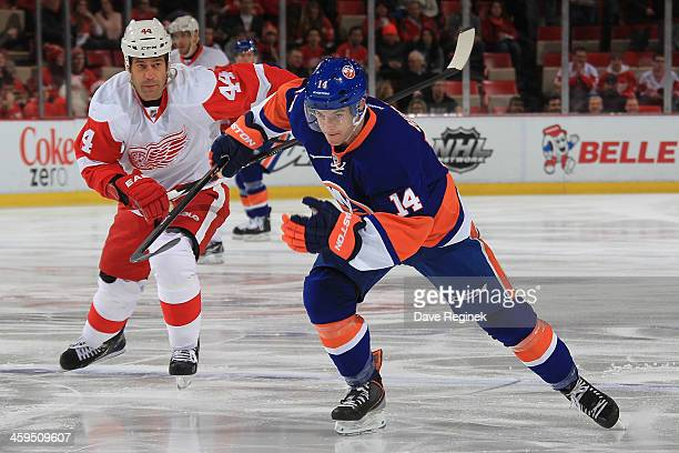 Thomas Hickey of the New York Islanders skates up ice in front of Todd Bertuzzi of the Detroit Red Wings during an NHL game at Joe Louis Arena on...