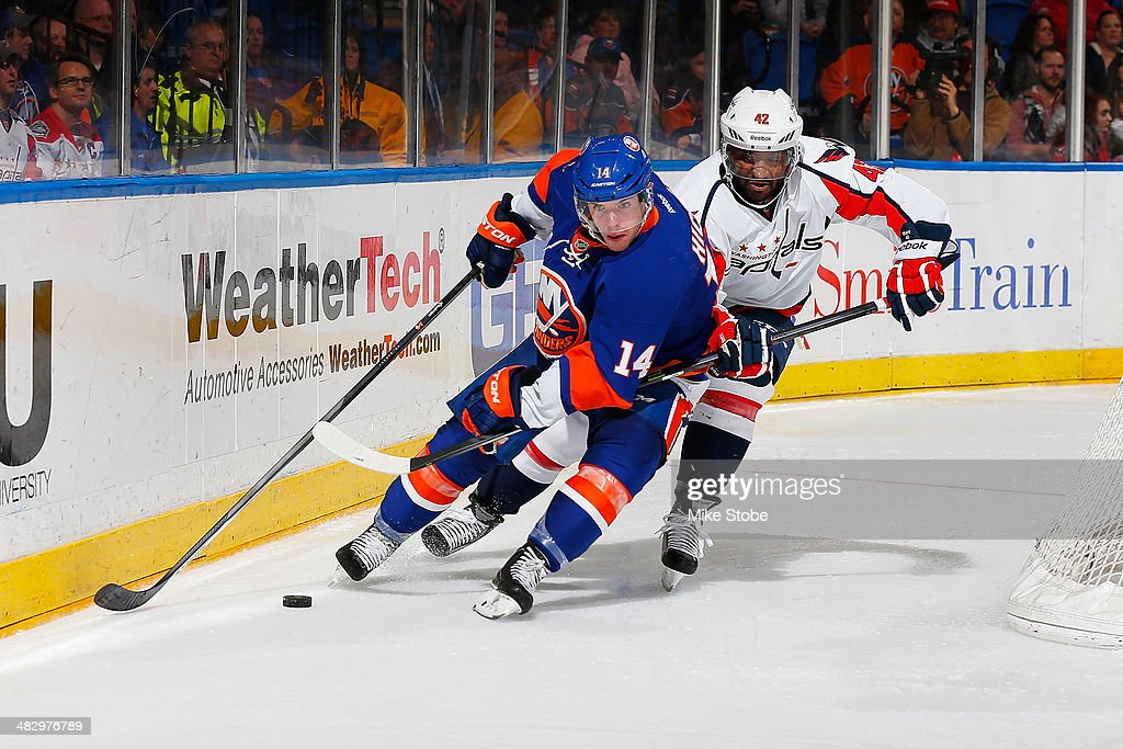 Thomas Hickey #14 of the New York Islanders skates with the puck as Joel Ward #42 of the Washington Capitals pursues him at Nassau Veterans Memorial Coliseum on April 5, 2014 in Uniondale, New York. The Capitals defeated the Islanders 4-3.