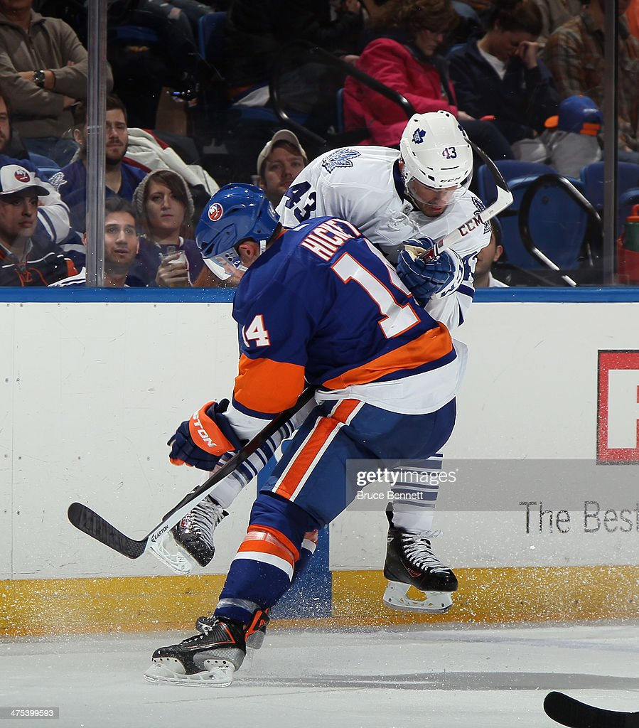 Thomas Hickey #14 of the New York Islanders throws a bodycheck into <a gi-track='captionPersonalityLinkClicked' href=/galleries/search?phrase=Nazem+Kadri&family=editorial&specificpeople=4043234 ng-click='$event.stopPropagation()'>Nazem Kadri</a> #43 of the Toronto Maple Leafs at the Nassau Veterans Memorial Coliseum on February 27, 2014 in Uniondale, New York. The Islanders defeated the Maple Leafs 5-4 in overtime.