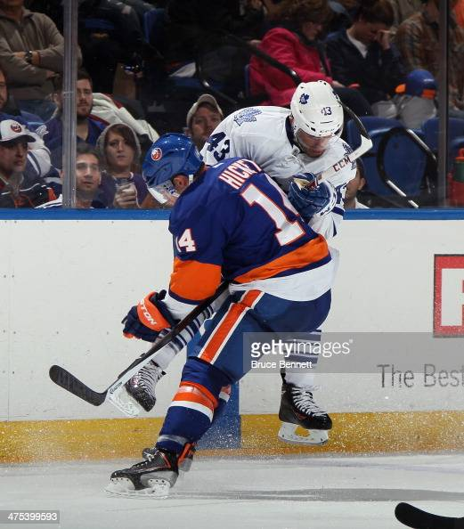 Thomas Hickey of the New York Islanders throws a bodycheck into Nazem Kadri of the Toronto Maple Leafs at the Nassau Veterans Memorial Coliseum on...