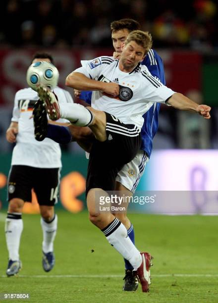 Thomas Hitzlsperger of Germany is challenged by Tim Sparv of Finland during the FIFA 2010 World Cup Group 4 Qualifier match between Germany and...