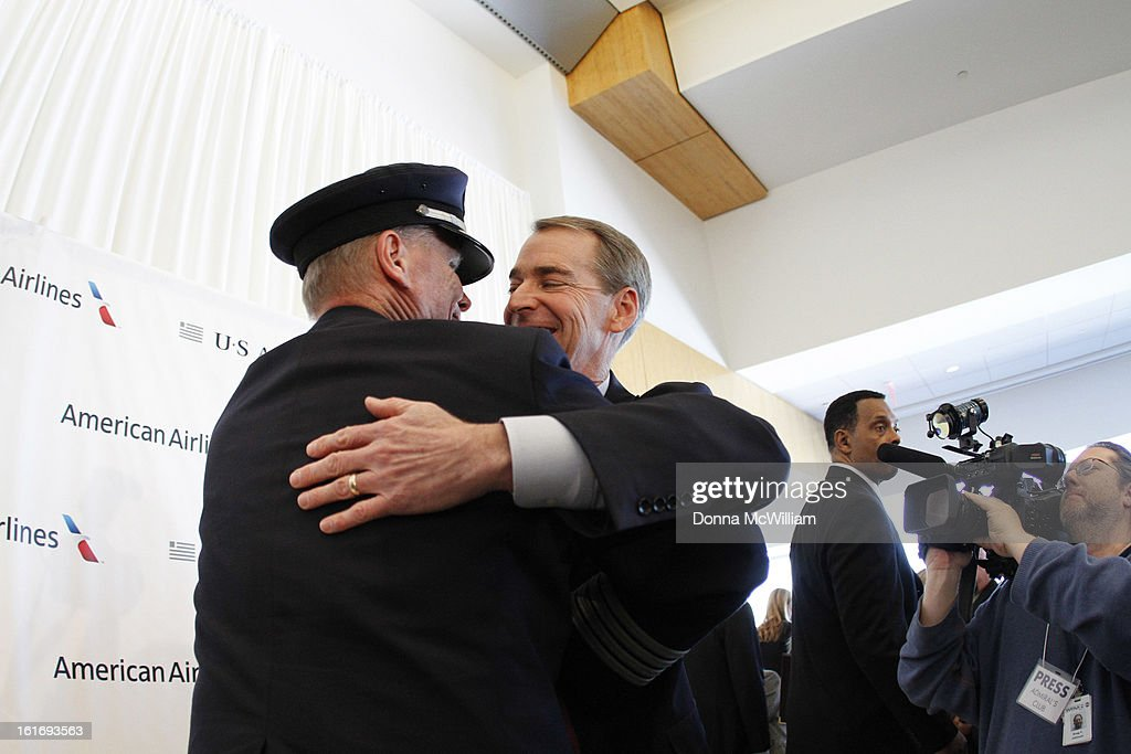 Thomas Horton (2nd L), Chairman, President and Chief Executive Officer of American Airlines, and Captain Anthony R. Chapman (L), Vice President of the Allied Pilots Association hug at the end of a news conference to announce the merger of American Airlines and US Airways, February 14, 2013 in Dallas Texas. US Airways and American Airlines have agreed to an $11 billion merger, creating the largest airline in the world. The airline will be called American Airlines and be headed by US Airways CEO Doug Parker. (Photo by Donna McWilliam/Getty Images