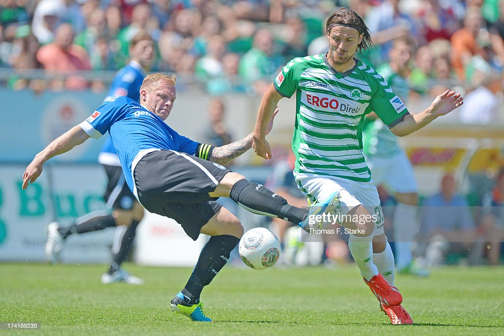 Thomas Huebener (L) of Bielefeld tackles Ilir Azemi of Fuerth during the Second Bundesliga match between Greuther Fuerth and Arminia Bielefeld at the Trolli Arena on July 21, 2013 in Fuerth, Germany.