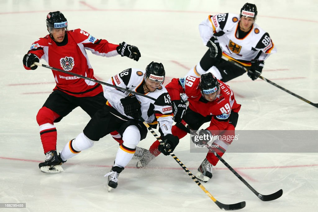 Thomas Hundertpfund (L) and Raphael Herburger (#89) of Austria and Frank Hordler (C) of Germany battle for the puck during the IIHF World Championship group H match between Austria and Germany at Hartwall Areena on May 8, 2013 in Helsinki, Finland.