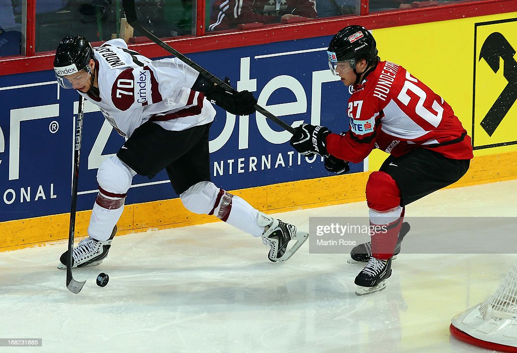 Thomas Hundertpfund (R) of Austria and Miks Indrasis (L) of Latvia battle for the puck during the IIHF World Championship group H match between Austria and Latvia at Hartwall Areena on May 7, 2013 in Helsinki, Finland.