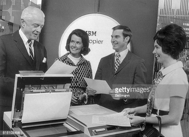 Thomas J Watson Jr chairman of the board of IBM and his wife Olive examine the company's new and improved office copying machine with stockholders Mr...