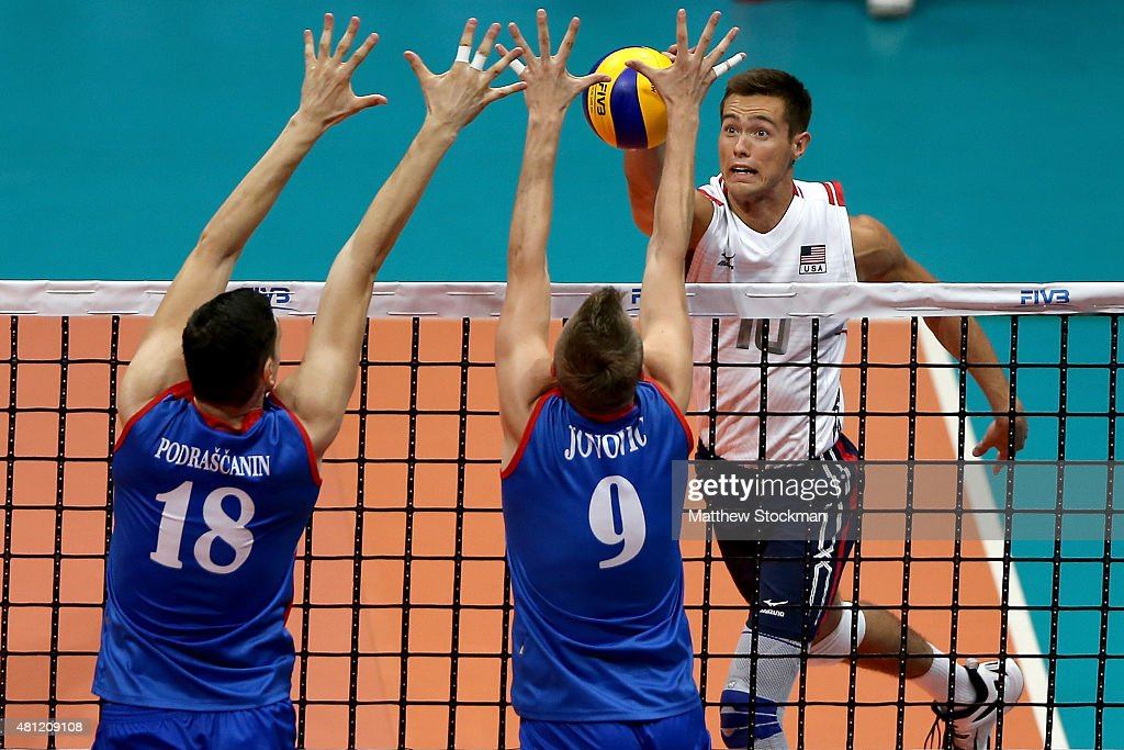 Thomas Jaeschke of the United States spikes the ball against Marko Podrascanin and Nikola Jovovic of Serbia during the FIVB World League Group 1...
