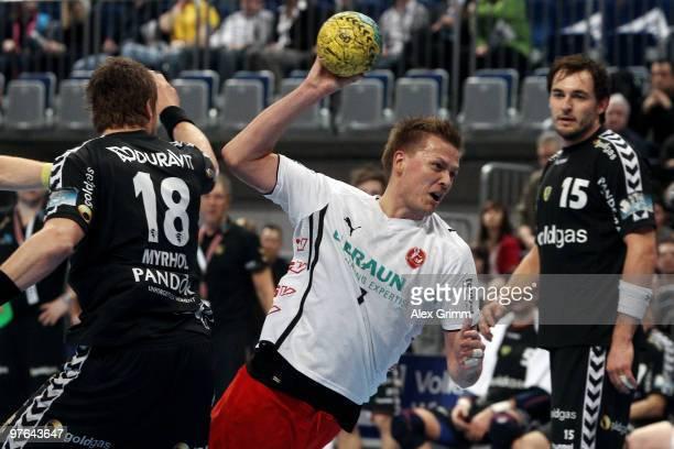 Thomas Klitgaard of Melsungen is challenged by Bjarte Myrhol and Michael Mueller of RheinNeckar Loewen during the Toyota Handball Bundesliga match...