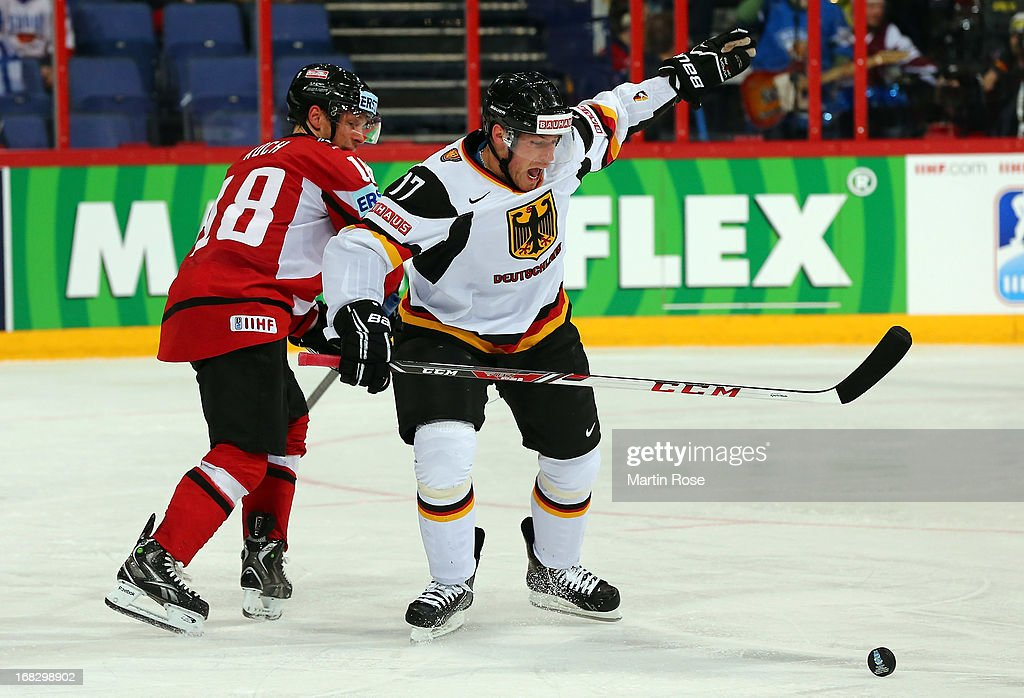 Thomas Koch (L) of Austria and Marcus Kink (R) of Germany battle for the puck during the IIHF World Championship group H match between Austria and Germany at Hartwall Areena on May 8, 2013 in Helsinki, Finland.