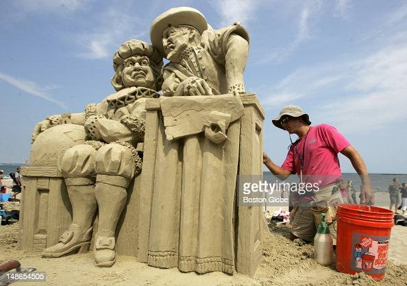 Thomas Koet of Melbourne Fla puts the finishing touches on his sand sculpture called 'It's Round It's Flat' during Saturday's sand castle competition...