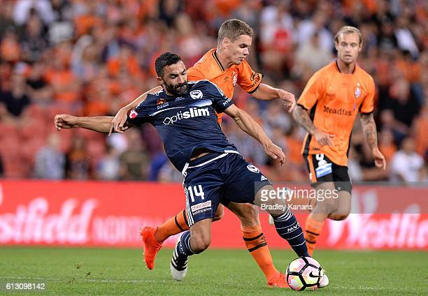 Thomas Kristensen of the Roar and Fahid Ben Khalfallah of the Victory challenge for the ball during the round one ALeague match between the Brisbane...