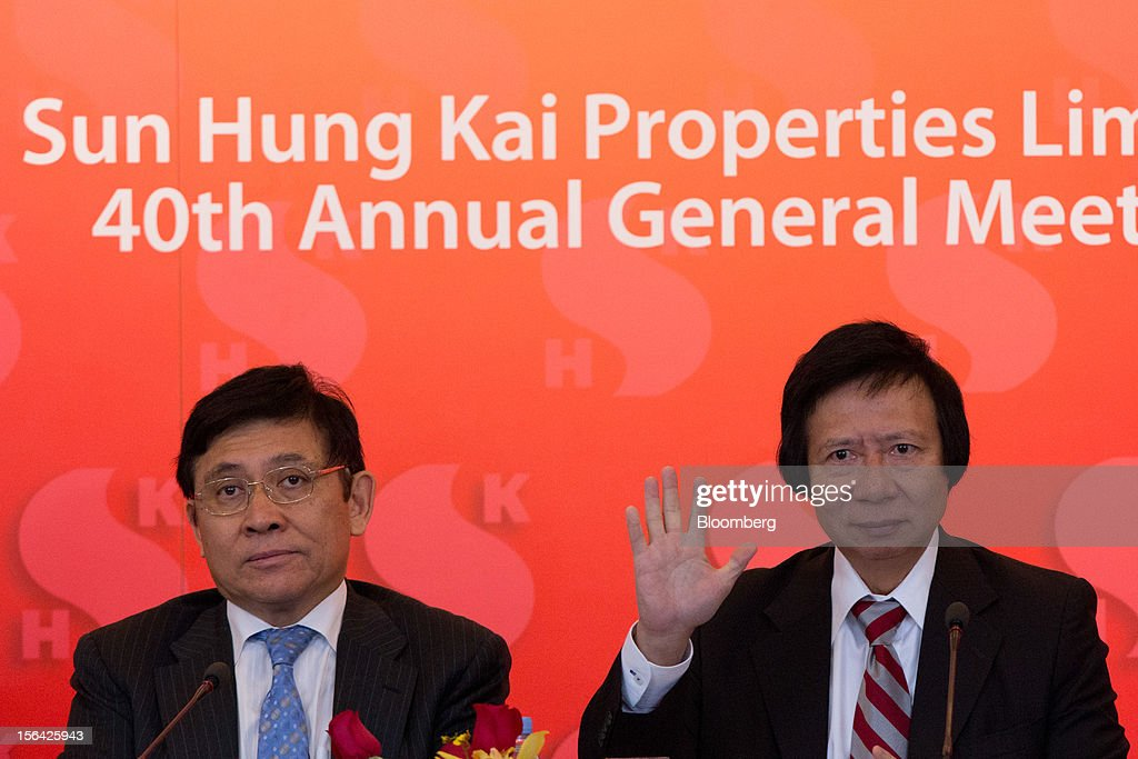 Thomas Kwok, co-chairman of Sun Hung Kai Properties Ltd., right, raises his hand while Raymond Kwok, co-chairman, looks on during a news conference in Hong Kong, China, on Thursday, Nov. 15, 2012. Sun Hung Kai will continue buying land in Hong Kong, says Thomas Kwok. Photographer: Lam Yik Fei/Bloomberg via Getty Images