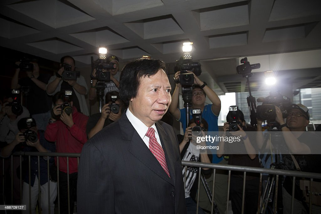 Thomas Kwok, co-chairman of Sun Hung Kai Properties Ltd., stands for members of the media at the entrance to the High Court in Hong Kong, China, on Thursday, May 8, 2014. Thomas and Raymond Kwok, the billionaire brothers running Hong Kongs second-largest developer, are set to go on trial today for bribing Rafael Hui, the Chinese citys former No. 2 official. All three men have pleaded not guilty and denied all charges. Photographer: Brent Lewin/Bloomberg via Getty Images