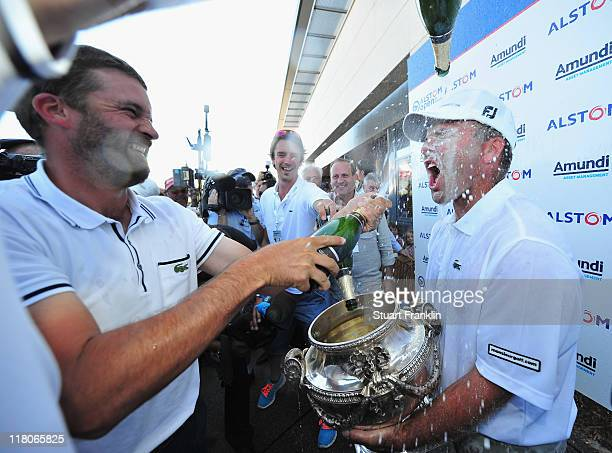 Thomas Levet of France is showered in champagne by Francois Delamontagne of France after being presented with the trophy for winning The Open de...