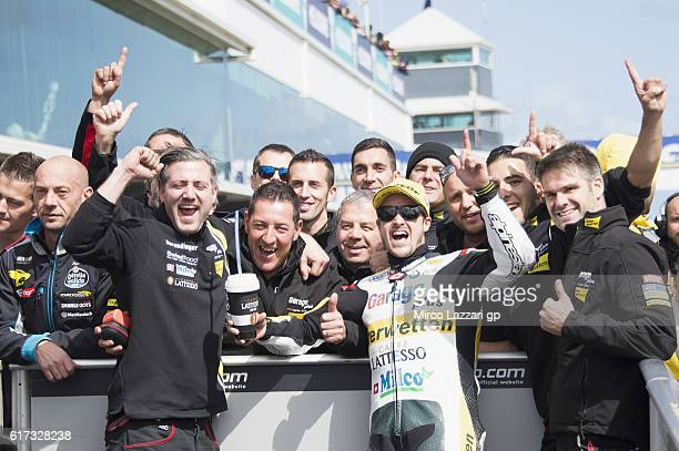 Thomas Luthi of Switzerland and Garage Plus Interwetten celebrates the victory with team under the podium at the end of the Moto2 race during the...