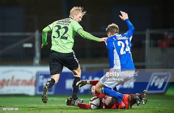Thomas Mikkelsen of Vejle Boldklub Goalkeeper Viktor Noring of Lyngby Boldklub and Thomas Sorensen of Lyngby Boldklub compete for the ball during the...