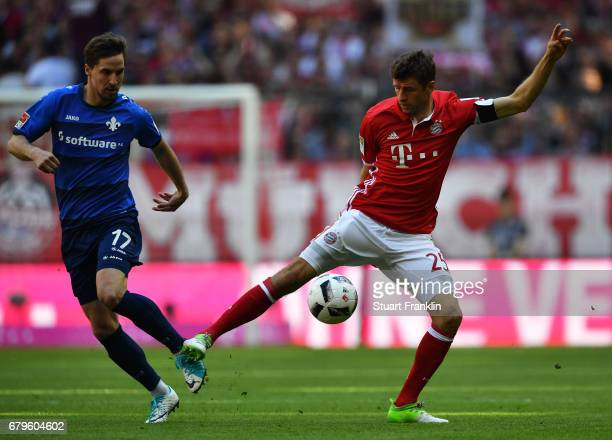 Thomas Mller of Muenchen is challenged by Sandro Sirigu of Dramstadt during the Bundesliga match between Bayern Muenchen and SV Darmstadt 98 at...
