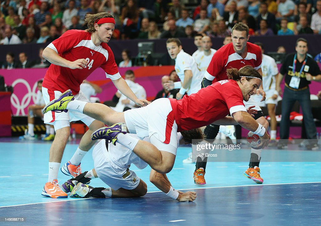 <a gi-track='captionPersonalityLinkClicked' href=/galleries/search?phrase=Thomas+Mogensen&family=editorial&specificpeople=4060426 ng-click='$event.stopPropagation()'>Thomas Mogensen</a> of Denmark dives through the Spain defence during the Men's Handball Preliminary match between Denmark and Spain on Day 4 of the London 2012 Olympic Games at The Copper Box on July 31, 2012 in London, England.