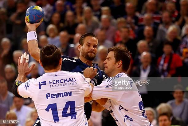 Thomas Mogensen of Flensburg challenges Evgeni Pevnov and Mark Bult of Gummersbach for the ball during the DKB HBL Bundesliga match between SG...