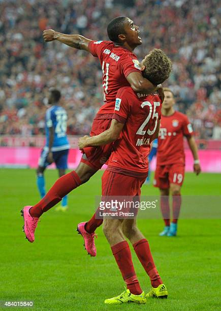 Thomas Mueller and Douglas Costa of FC Bayern Muenchen celebrate scoring their team's third goal during the Bundesliga match between FC Bayern...