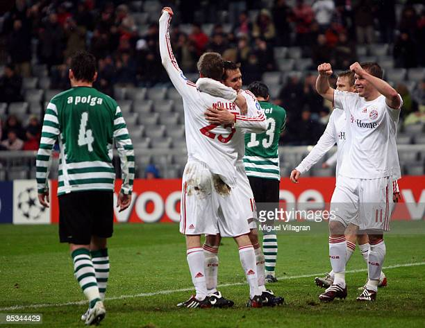 Thomas Mueller and his team mates Miroslav Klose and Lukas Podolski of Muenchen celebrate Mueller's goal as Anderson Polga and Tonel of Lisbon walk...