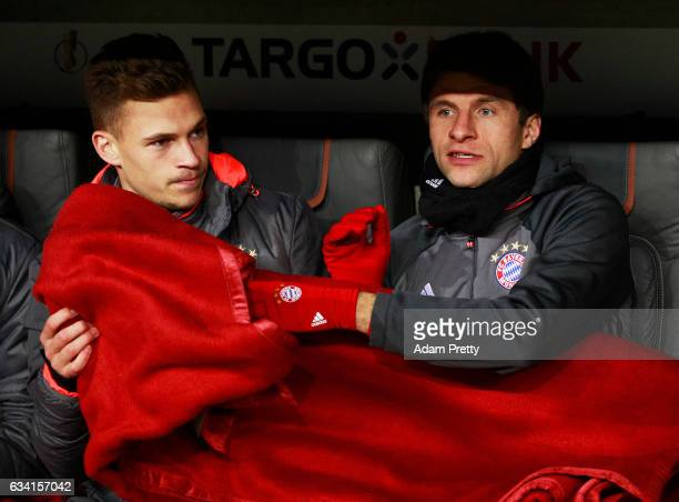 Thomas Mueller and Joshua Kimmich of Bayern Muenchen sit on the bench before the DFB Cup Round Of 16 match between Bayern Muenchen and VfL Wolfsburg...