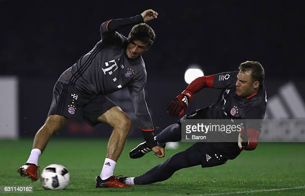 Thomas Mueller is challenged by goalkeeper Manuel Neuer during a training session at day 5 of the Bayern Muenchen training camp at Aspire Academy on...