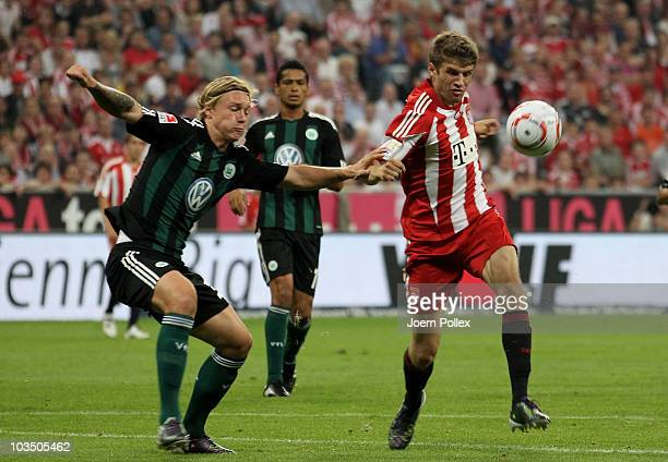 Thomas Mueller of Bayern and Simon Kjaer of Wolfsburg battle for the ball during the Bundesliga match between FC Bayern Muenchen and VfL Wolfsburg at...