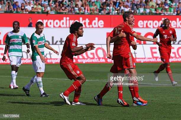 Thomas Mueller of Bayern celebrates the first goal with Holger Badstuber and Dante of bayern during the Bundesliga match between Greuther Fuerth and...