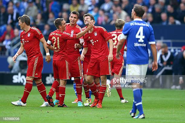 Thomas Mueller of Bayern celebrates the second goal with Philipp Lahm and Mario Mandzukic of Bayern during the Bundesliga match between FC Schalke 04...