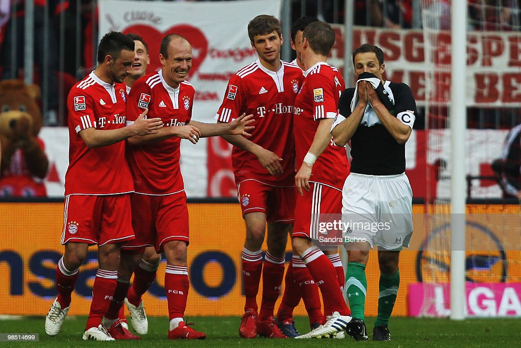 Thomas Mueller of Bayern celebrates with team mates after scoring the third goal while Steven Cherundolo of Hannover looks dejected during the...