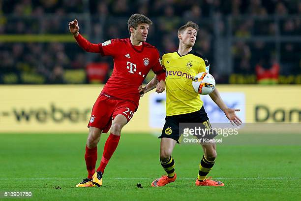 Thomas Mueller of Bayern challenges Erik Durm of Dortmund during the Bundesliga match between Borussia Dortmund and FC Bayern Muenchen at Signal...