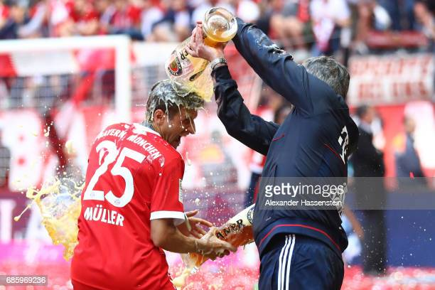 Thomas Mueller of Bayern Muenchen and Carlo Ancelotti Manager of Bayern Muenchen shower each other in beer following the Bundesliga match between...