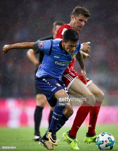 Thomas Mueller of Bayern Muenchen and Charles Aranguiz of Leverkusen battle for the ball during the Bundesliga match between FC Bayern Muenchen and...