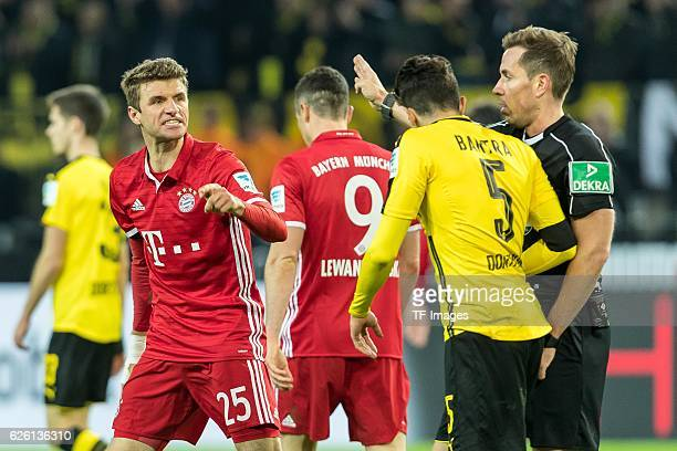 Thomas Mueller of Bayern Muenchen and Marc Bartra of Borussia Dortmund gestures during the Bandesliga soccer match between BV Borussia Dortmund and...