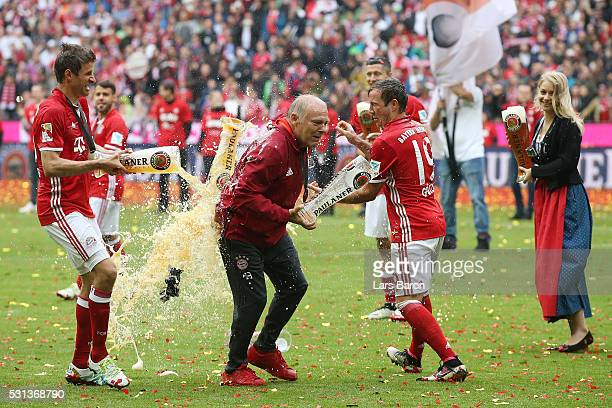 Thomas Mueller of Bayern Muenchen and Mario Goetze of Bayern Muenchen throw beer at Assistant Coach Hermann Gerland in celebration following the...