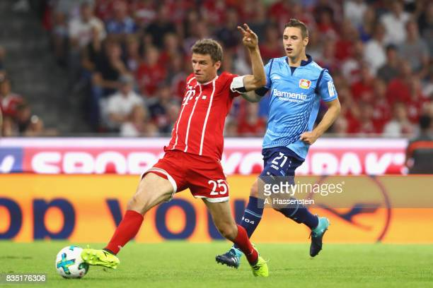 Thomas Mueller of Bayern Muenchen battles for the ball with Dominik Kohr of Leverkusen during the Bundesliga match between FC Bayern Muenchen and...
