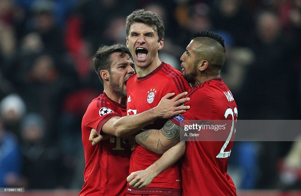 Thomas Mueller (C) of Bayern Muenchen celebrates his first goal with teammates Juan Bernat (L) and Arturo Vidal during the Champions League round of 16 second leg match between FC Bayern Muenchen and Juventus Turin at Allianz Arena on March 16, 2016 in Munich, Germany.