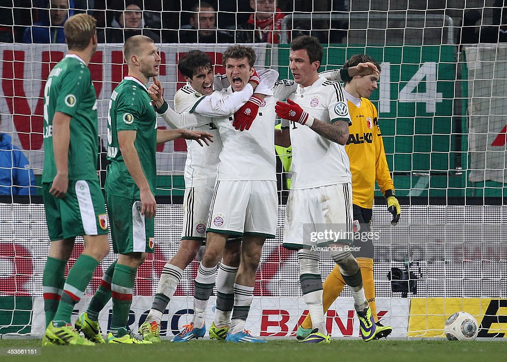 Thomas Mueller (3rdR) of Bayern Muenchen celebrates his goal with his teammates Javi Martinez (3rdL) and Mario Mandzukic (2ndR) as Augsburg's goalkeeper Marwin Hitz (R) reacts during their DFB Cup round of 16 match between FC Augsburg and FC Bayern Muenchen at SGL Arena on December 4, 2013 in Augsburg, Germany.