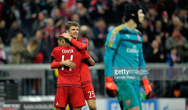 Thomas Mueller of Bayern Muenchen celebrates with Douglas Costa of Bayern Muenchen on the final whistle during the UEFA Champions League Group F...