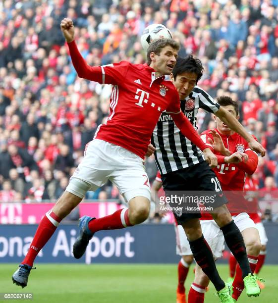 Thomas Mueller of Bayern Muenchen goes up for a header with Makoto Hasebe of Frankfurt during the Bundesliga match between Bayern Muenchen and...