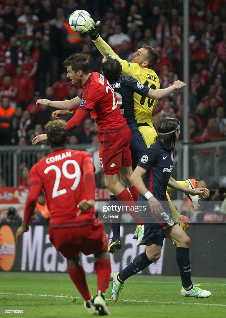 Thomas Mueller (2ndL) of Bayern Muenchen heads for the ball with goalkeeper Jan Oblak (2ndR) of Atletico Madrid during the Champions League semi final second leg match between FC Bayern Muenchen and Club Atletico de Madrid at Allianz Arena on May 3, 2016 in Munich, Germany.
