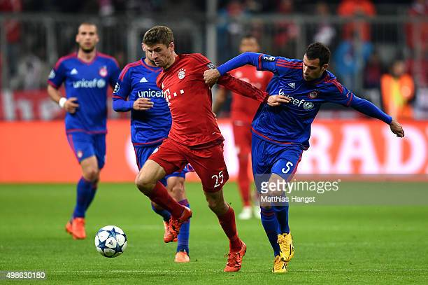 Thomas Mueller of Bayern Muenchen holds off the challenge from Luka Milivojevic of Olympiacos during the UEFA Champions League group F match between...