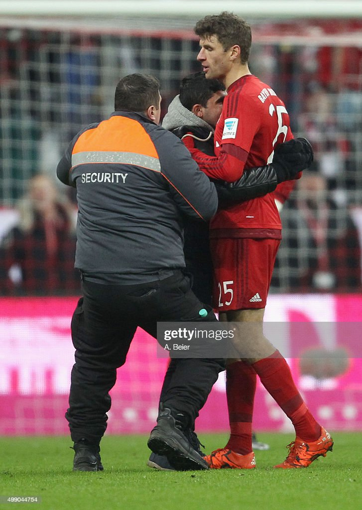 Thomas Mueller (R) of Bayern Muenchen is hugged by a pitch invader during the Bundesliga match between FC Bayern Muenchen and Hertha BSC at Allianz Arena on November 28, 2015 in Munich, Germany.