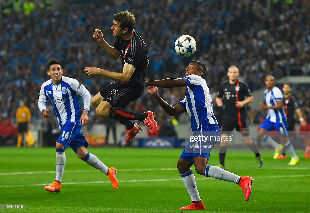 Thomas Mueller of Bayern Muenchen jumps with Alex Sandro of FC Porto during the UEFA Champions League Quarter Final first leg match between FC Porto...