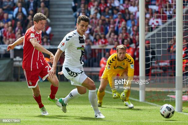 Thomas Mueller of Bayern Muenchen MarcOliver Kempf of Freiburg and Goalkeeper Alexander Schwolow of Freiburg battle for the ball during the...